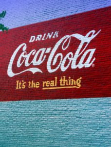 Coke the Real Thing painted on a wall