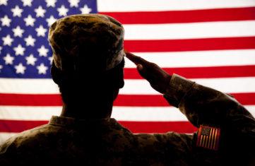 Serviceman saluting an American flag